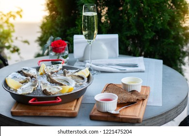 Fresh oysters with lemon's slices in ice and champagne. Restaurant delicacy, beautiful table setting. Saltwater oysters dish. Romantic dinner in restaurant.