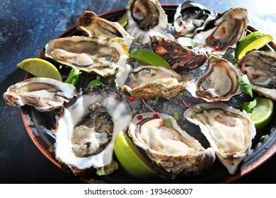 Fresh oysters with lime on a round plate. Oyster season. Macro-seafood dish. Oyster on the half shell.Two varieties of oysters.Out of focus.