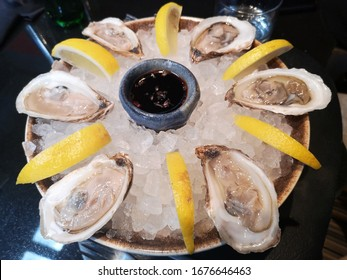 Fresh oysters on an ice plate served with lemon