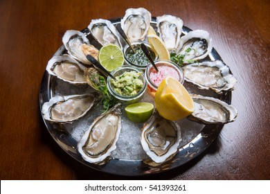 Fresh oysters on a plate with ice, lemon, lime and souces on a wooden table