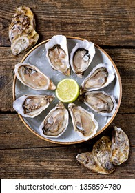 Fresh oysters with slices of lemon on ice on old wooden background. Top view.