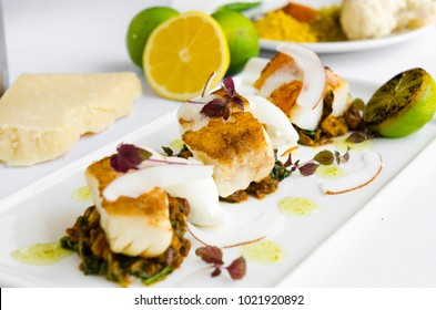 Fresh pan seared, crispy golden cod fish fillet, served on a bed of curried cauliflower, spinach and potato. A beautiful seafood dish.