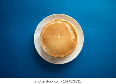 Fresh pancakes on a white dish. Classic blue background. Flat lay