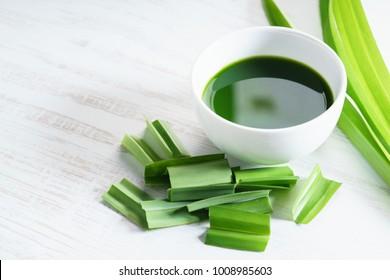 fresh pandan leaves and pandan juice on white wooden background