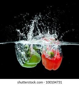 Fresh  paprika splash in water on black background