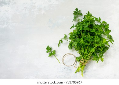 Fresh parsley on a light stone or slate background. Top view with copy space, flat lay.