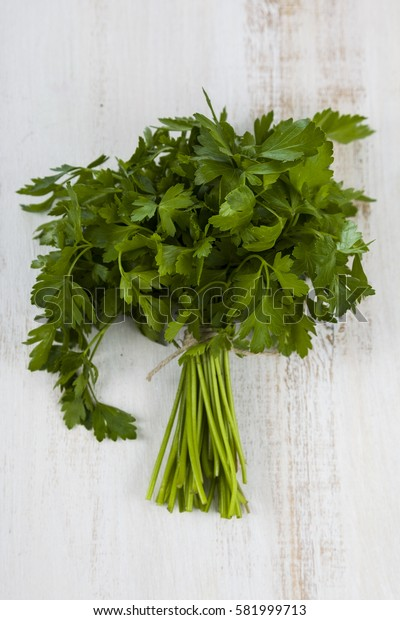 Fresh parsley on a light wooden background. Herbs for cooking various dishes close up.