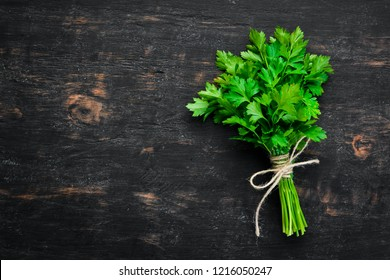 Fresh parsley. Top view. On a black wooden background. Free space for text.