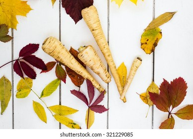 Fresh parsnips and colourful autumn leaves on white wooden boards, top view