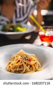 Fresh pasta aglio olio in summer garden restaurant on sunny day lunch