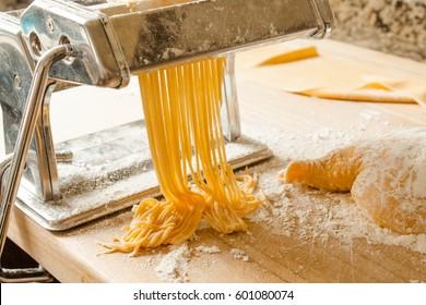 Fresh pasta spaghetti home making machine with dough, spaghetti, wheat flour and cooking table