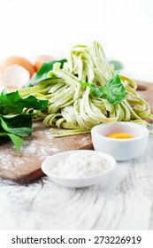 Fresh pasta tagliatelle with spinach leaves, vegetables and eggs on white wooden background, selective focus