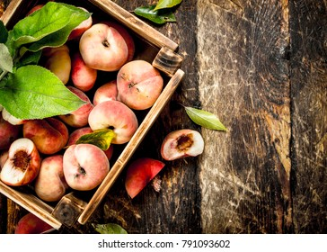 Fresh peaches in a box. On a wooden background.
