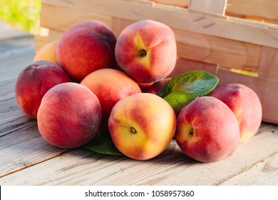 Fresh peaches fruits with leaves  on wooden rustic background