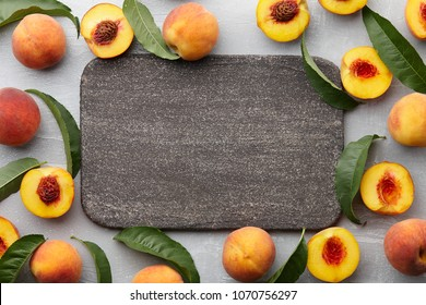 Fresh peaches fruits with leaves on textured stone background, top view