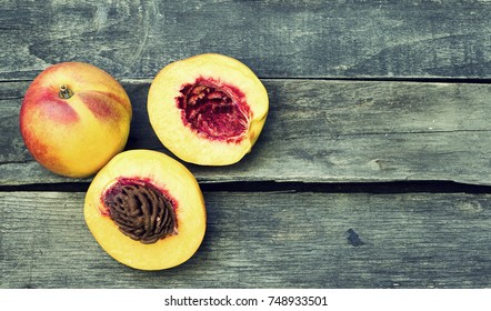 Fresh peaches fruits on dark wooden rustic background- top view, vintage look