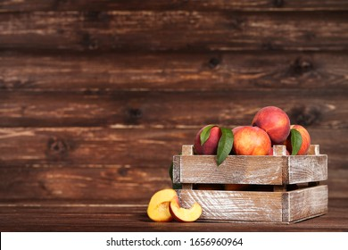 Fresh peaches with green leafs in crate on brown wooden table
