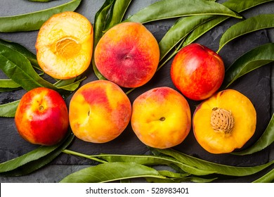Fresh peaches with fresh leaves on black stone slate plate on gray stone slate background. Summer peaches. Top view