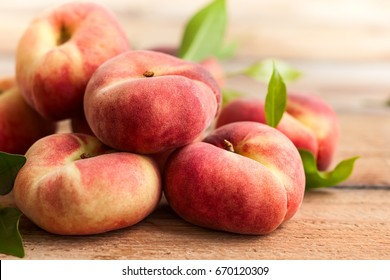 Fresh peaches with leaves on wooden background. Doughnut or vineyard type of flat peach.