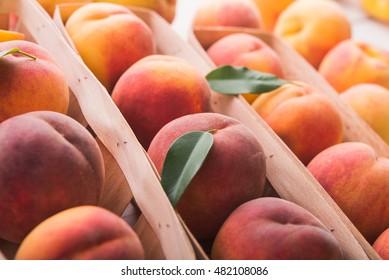fresh peaches on wooden basket