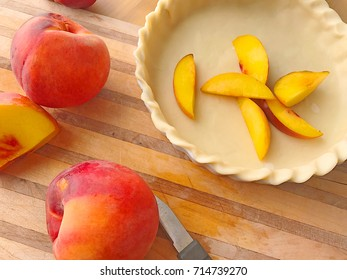 Fresh peaches, whole and sliced, with raw pie crust on cutting board