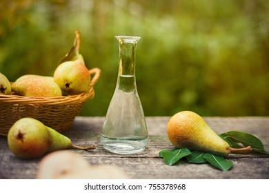 Fresh pear with bottle of fruit brandy on the table