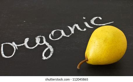 Fresh pear on blackboard and word organic written  by white chalk
