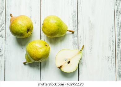 Fresh pears and half pear on the white wooden background.  Top view