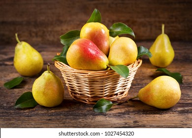 fresh pears with leaves in a basket on wooden background