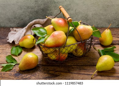 fresh pears with leaves in a basket on wooden table