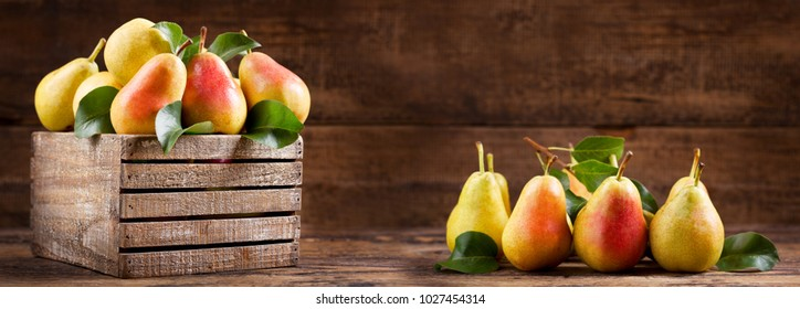 fresh pears with leaves in a wooden box on wooden background