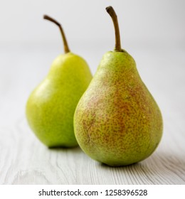 Fresh pears on a white wooden table, side view. Close-up.