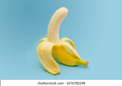 Fresh peeled banana on blue background
