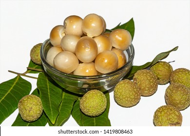 Fresh peeled longan fruits in a glass bowl on white isolated background with green leaves and longan.