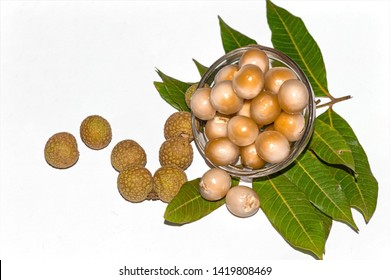 Fresh peeled longan fruits in a glass bowl on white isolated background with green leaves and longan.Top view and copy space.