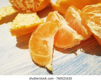 Fresh peeled and unpeeled mandarins or tangerines on the white wooden table
