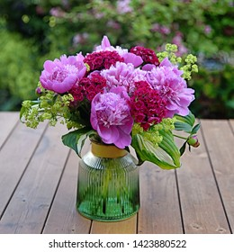 Fresh peony flowers in garden. Pink peonies in vase on wooden floor and bokeh background.