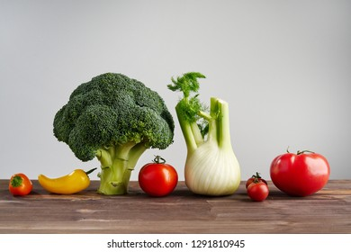 Fresh peper, broccoli, tomato on wooden background. Still life with raw vegetable. Concept of healthy food and nutrition.