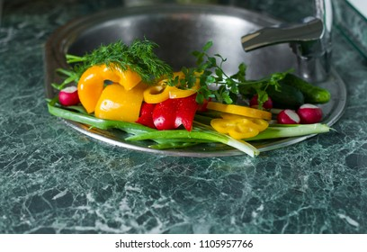 Fresh pepper, cucumber, parsley, dill and onions on the sink in a kitchen interior. vegetarian concept. washing vegetables. Preparation of fresh salad.