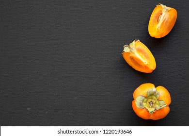 Fresh persimmon on black background, top view. Copy space.