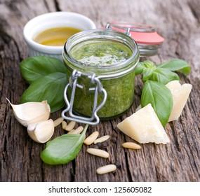 Fresh pesto with basil on wooden ground