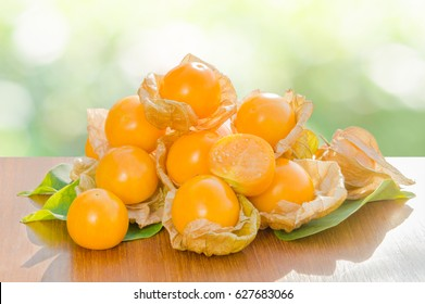 Fresh pichuberry (Cape Gooseberry), very delicious and healthy berry fruit, uchuva on brown wooden table and leaves with nature light green bokeh background in the garden or farm