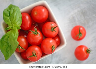 Fresh picked organic cherry tomatoes with vibrant basil leaves in square white dish on grey wooden background.  Healthy eating concept in flatlay composition.