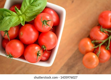 Fresh picked organic cherry tomatoes with vibrant basil leaves in square white dish on wooden background.  Healthy eating concept in flatlay composition.