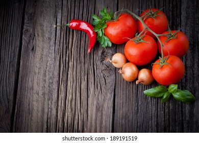 Fresh picked tomatoes and ketchup ingredients composition. Vegetables photography taken on rustic old table.