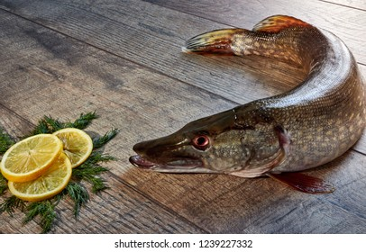Fresh pike fish on a wooden table with spices, dill, and lemon. Close up top view