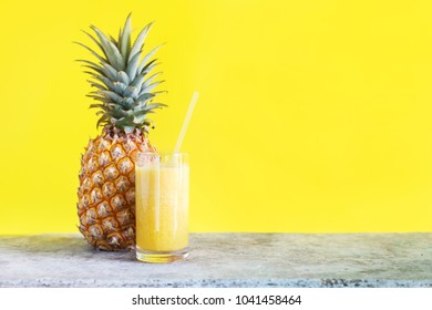 Fresh Pine Apple Juice Smoothie in Glass with Straw from Tropical Fruits Yellow Background Diet Concept