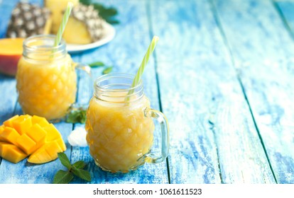 Fresh pineapple and mango smoothie in two glasses with fruits on a torquise wooden rustic background. Freshly blended summer drinks nice to energize during a hot day.