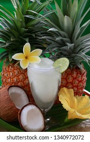 Fresh pineapple, opened coconut and Pina Colada tropical alcohol drink decorated with plumeria flower and lime slice