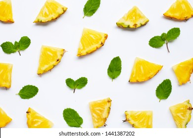 Fresh pineapple slices with mint leaves on white background.